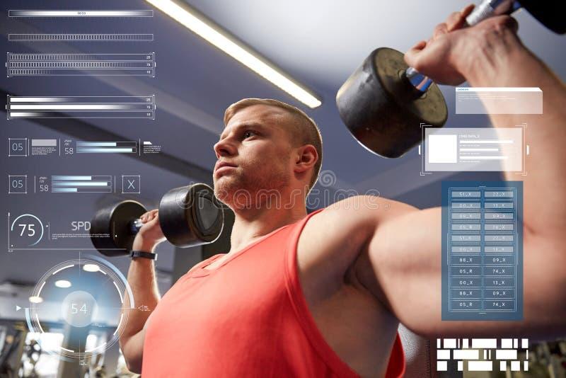 Młody człowiek napina mięśnie w gym z dumbbells zdjęcie stock