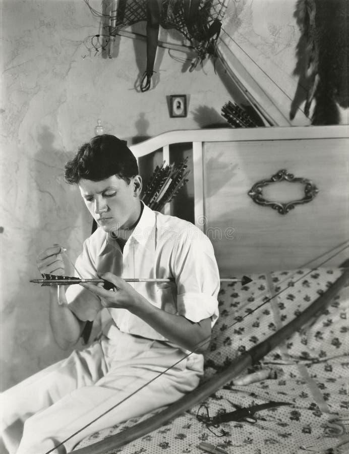 Młody człowiek naprawia jego strzała i łęk zdjęcie royalty free
