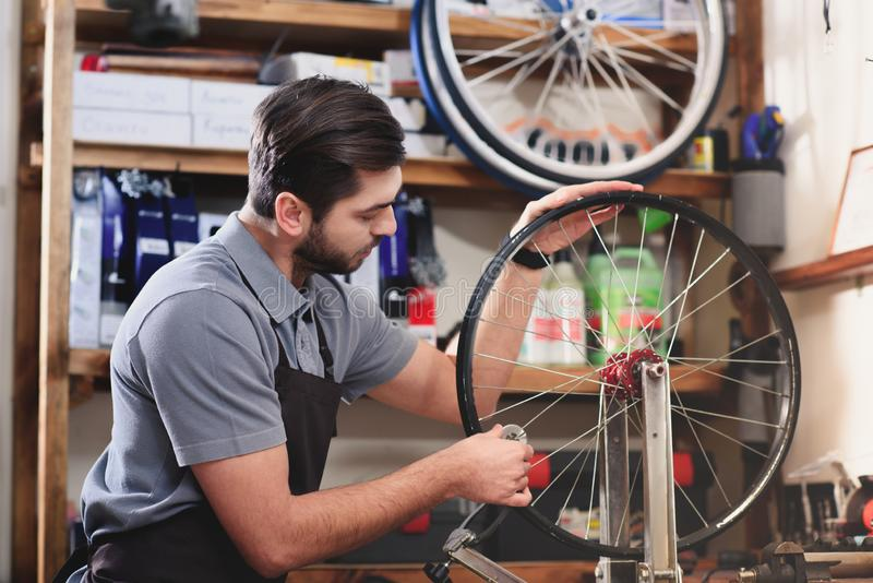 młody człowiek naprawia rowerowego koło w fartuchu zdjęcie stock