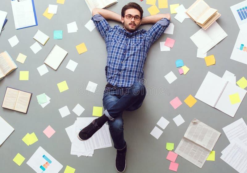 Młody człowiek odizolowywający na popielatym tle z papierami i notatkami relaksował przyglądającą kamerę zdjęcia royalty free
