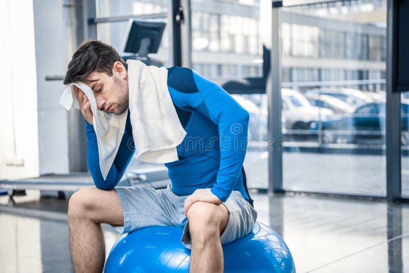 Młody człowiek odpoczywa na sprawności fizycznej piłce przy gym obraz stock