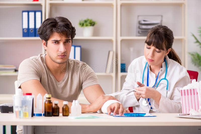 Młody człowiek odwiedza kobiet doktorskich traumatologis z bandażującą ręką obraz stock