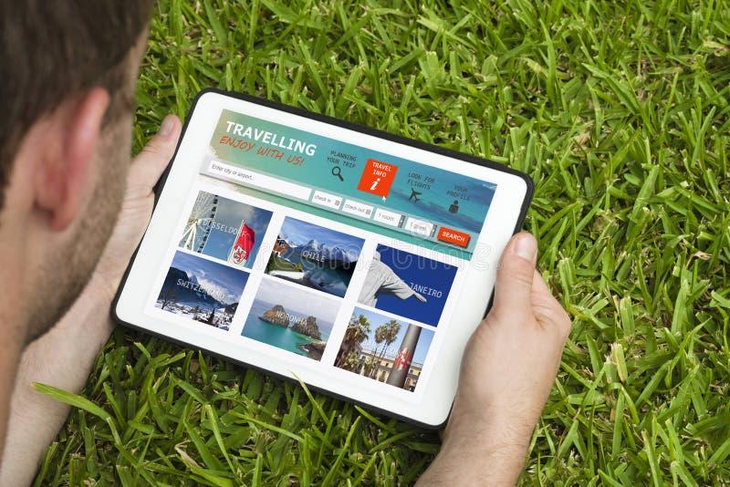 Młody człowiek odwiedza podróży stronę internetową trzyma pastylka przyrząd obrazy royalty free