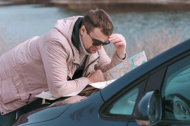Młody człowiek ogląda mapę drogową na kapiszonie samochód blisko rzeki zdjęcia royalty free