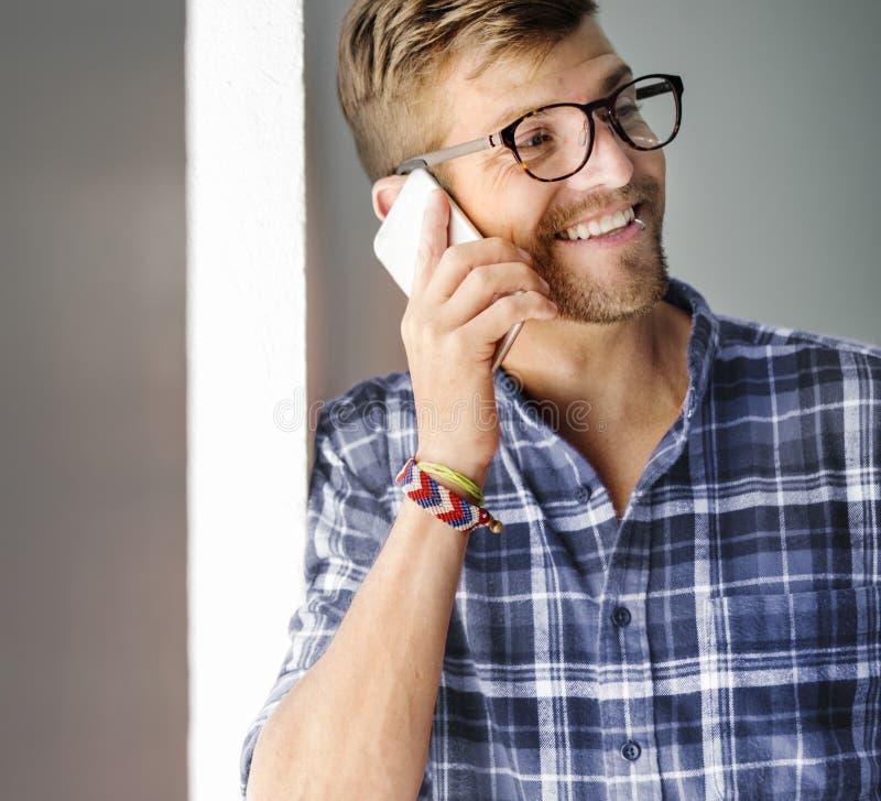 Młody Człowiek ono Uśmiecha się Opowiadający Smartphone pojęcie zdjęcie stock