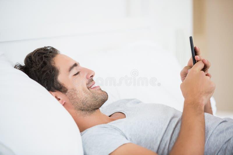 Młody człowiek ono uśmiecha się podczas gdy używać telefon komórkowego na łóżku zdjęcia stock