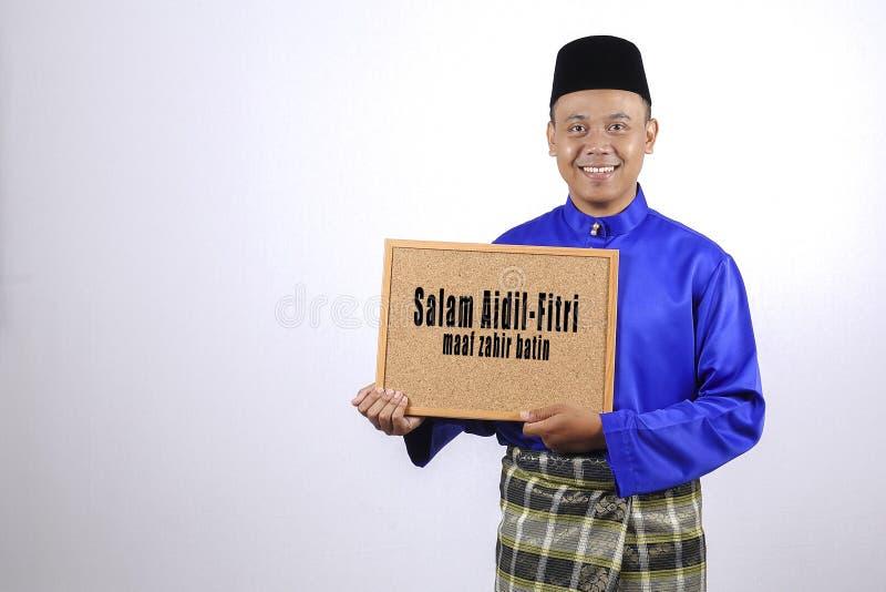 Młody człowiek ono uśmiecha się z chalkboard dla Eid Fitr lub Eid Adha sławy obrazy stock