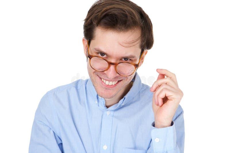 Młody człowiek ono uśmiecha się z szkłami i ręką twarzą obraz royalty free