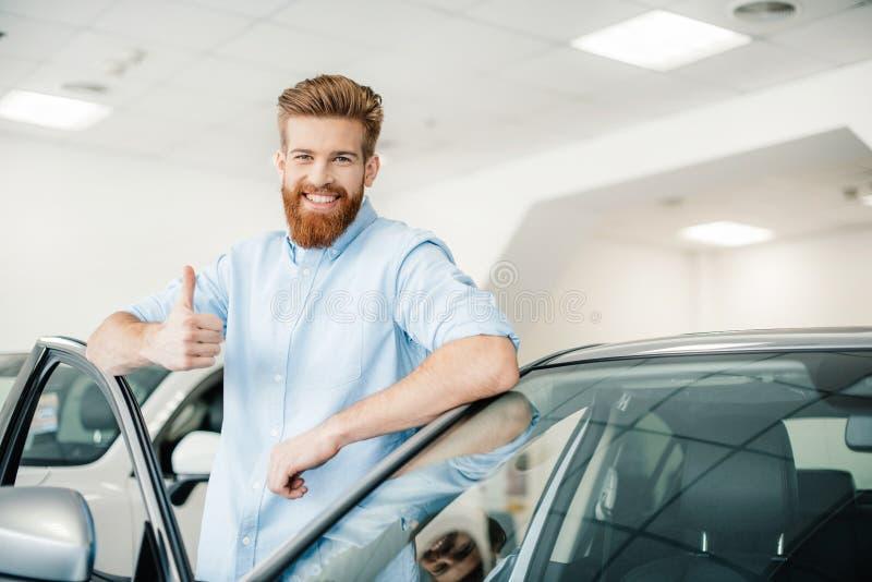 Młody człowiek opiera przy nowym samochodem i pokazuje kciuk up obrazy stock