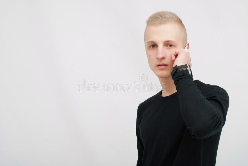 Młody człowiek opowiada na jego telefonie komórkowym odizolowywającym na białym tle obraz royalty free