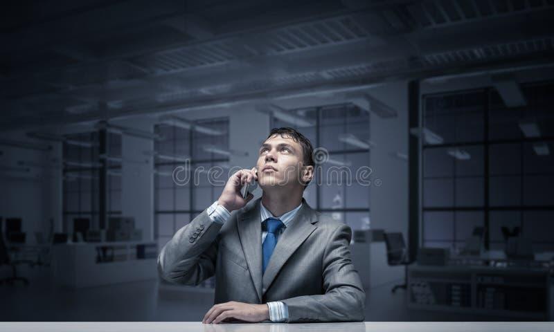 Młody człowiek opowiada na telefonie i patrzeje oddolny zdjęcia stock