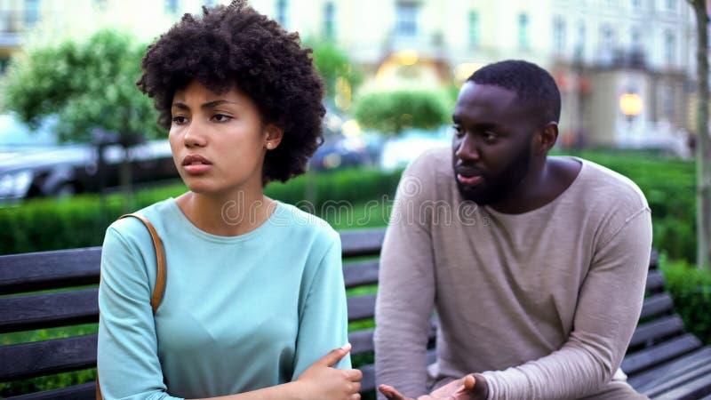 Młody człowiek opowiada obrażająca dziewczyna na ławce, z zazdrością kobieta, łama up zdjęcie stock