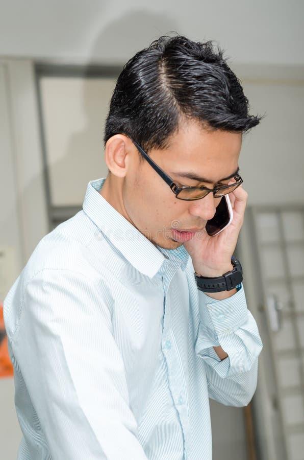 Młody Człowiek opowiada w ręka telefon. fotografia royalty free