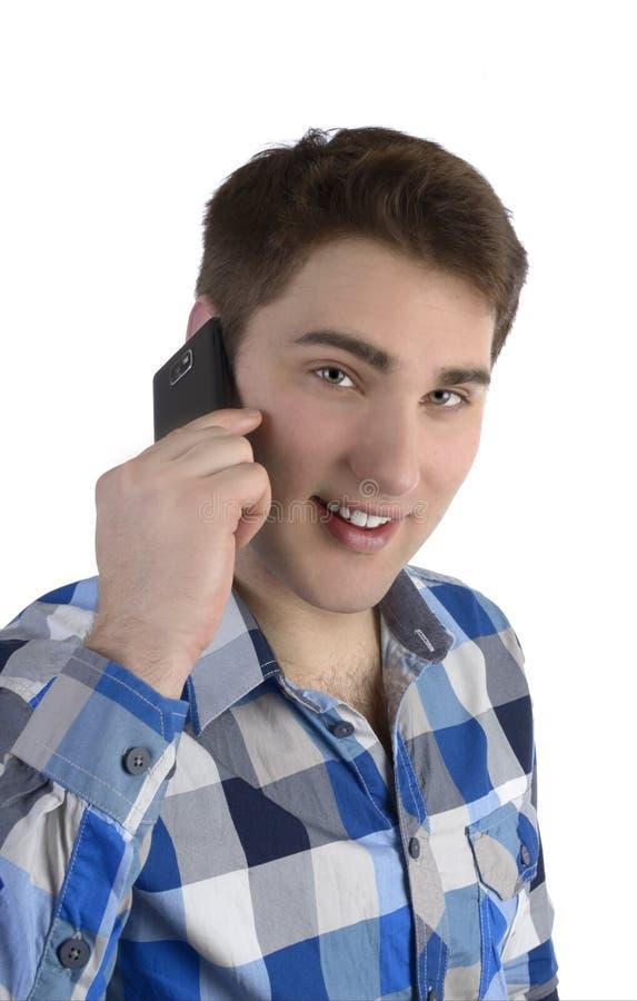 Młody człowiek opowiada z telefonem komórkowym w błękitnej koszula zdjęcia stock