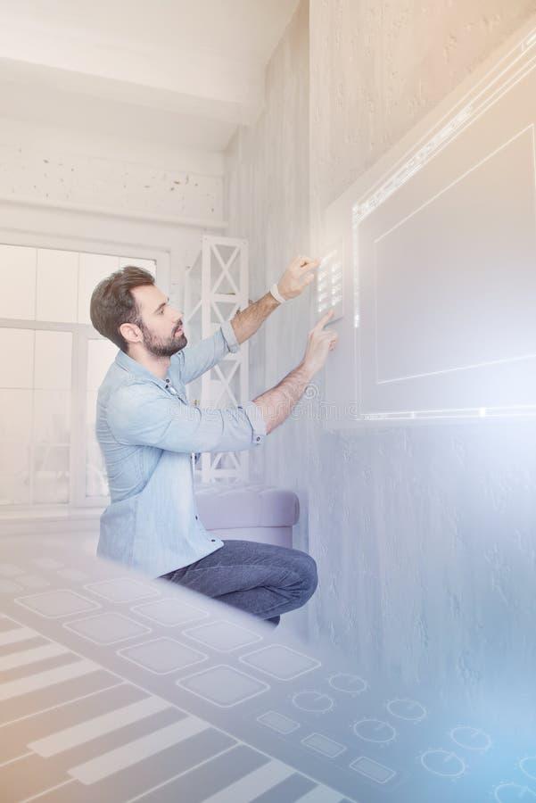 Młody człowiek ostrożnie dotyka system bezpieczeństwa podczas gdy być w mądrze domu obraz stock