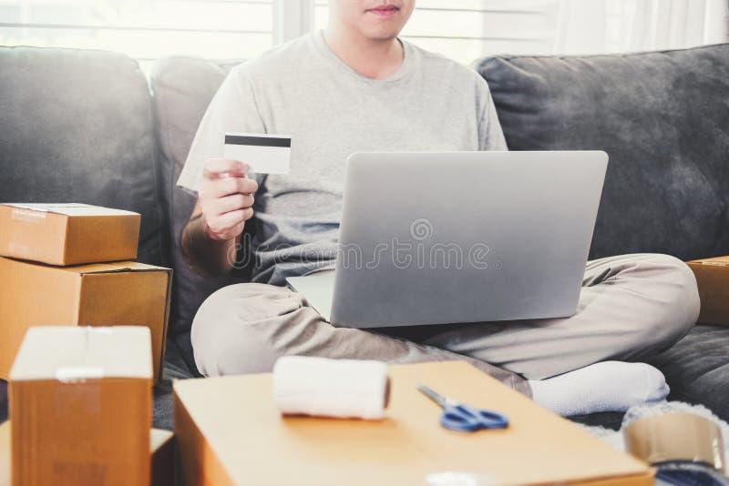 Młody człowiek otrzymywał online zakupy pakuneczek kartą kredytową, online marketing na zakupu małym biznesie w domu, Online bizn fotografia stock
