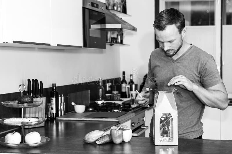 Młody człowiek otwiera pakunek świezi składniki robić zdrowemu gościowi restauracji obraz stock