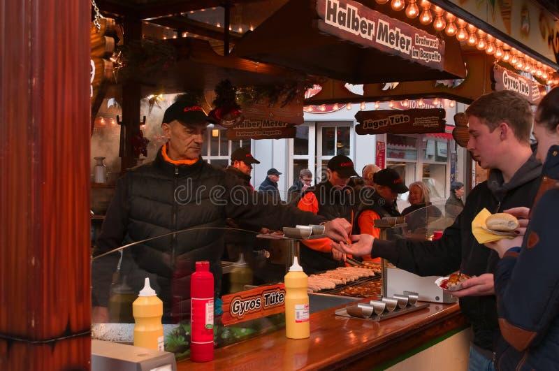 Młody człowiek płaci na Bożenarodzeniowym rynku w Goettingen, Niemcy obrazy royalty free
