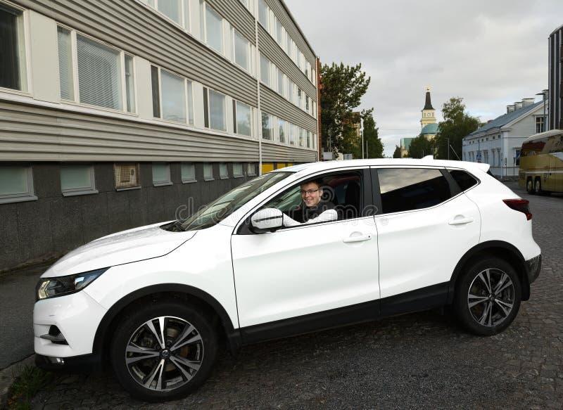 Młody człowiek parkuje białego samochód w Oulu obraz royalty free