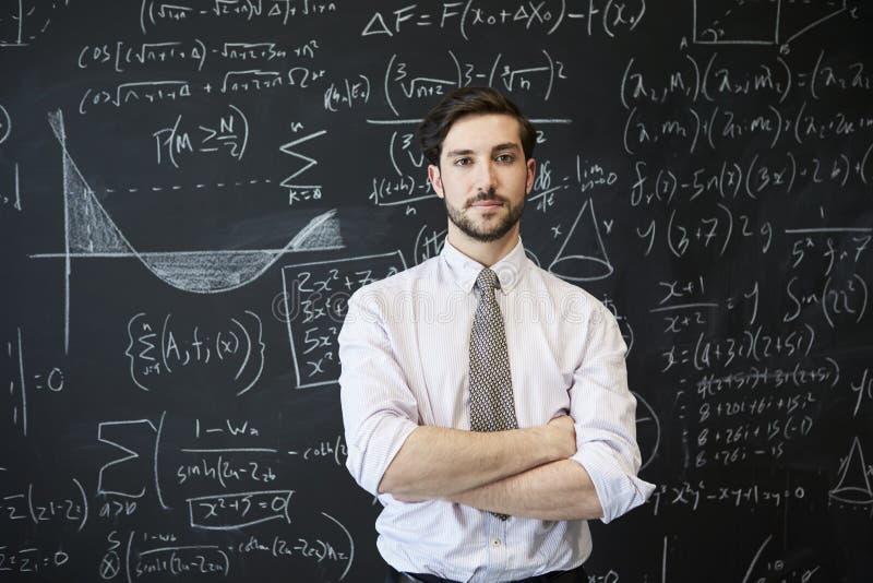 Młody człowiek patrzeje kamera przed blackboard obraz stock