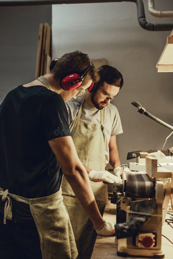 Młody człowiek patrzeje kolegi pracuje w joinery zdjęcia royalty free