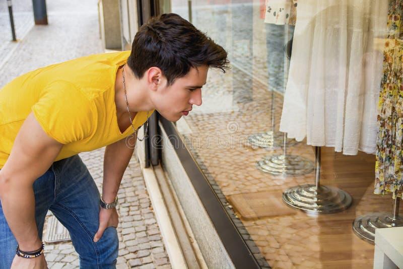 Download Młody Człowiek Patrzeje Mod Rzeczy W Sklepowym Okno Obraz Stock - Obraz złożonej z fantazja, model: 57654387