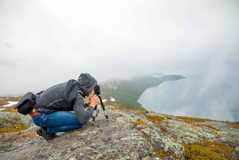 Młody człowiek patrzeje na panoramie natura widok z fjord i górami w chmurach, Norwegia obrazy stock