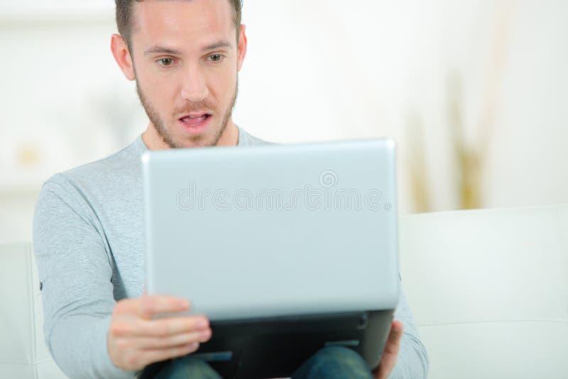 Młody człowiek patrzeje notatnika z zdziwionym wyrażeniem obraz stock
