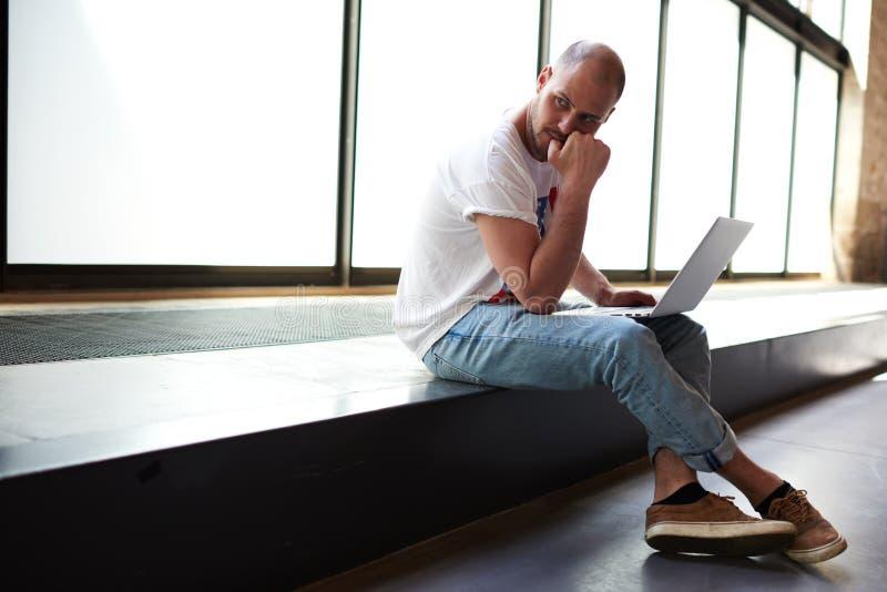 Młody człowiek patrzeje rozważny podczas gdy pracujący na laptopie trzyma mnie na kolanach obrazy royalty free