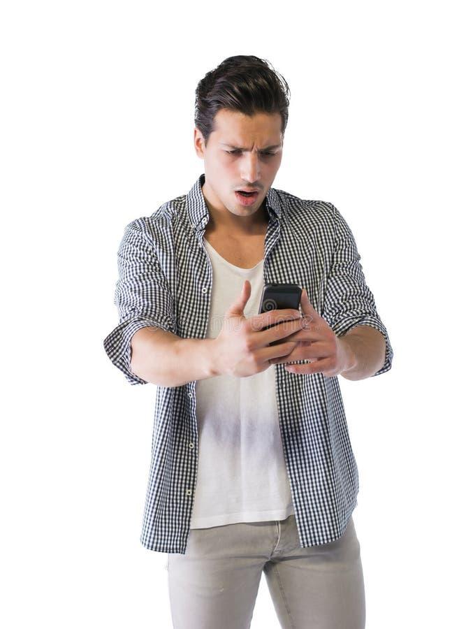 Młody człowiek patrzeje telefon komórkowego z gniewnym wyrażeniem obrazy stock