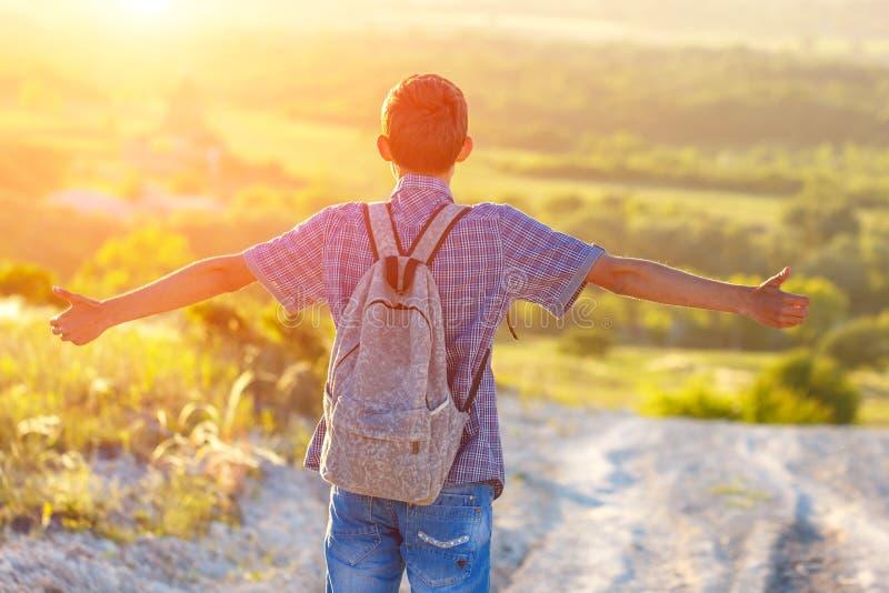 Młody człowiek patrzeje w odległość z plecakiem jest na drodze rozprzestrzenia jego ręki strona słońca ` s promieni połysk jaskra obrazy royalty free
