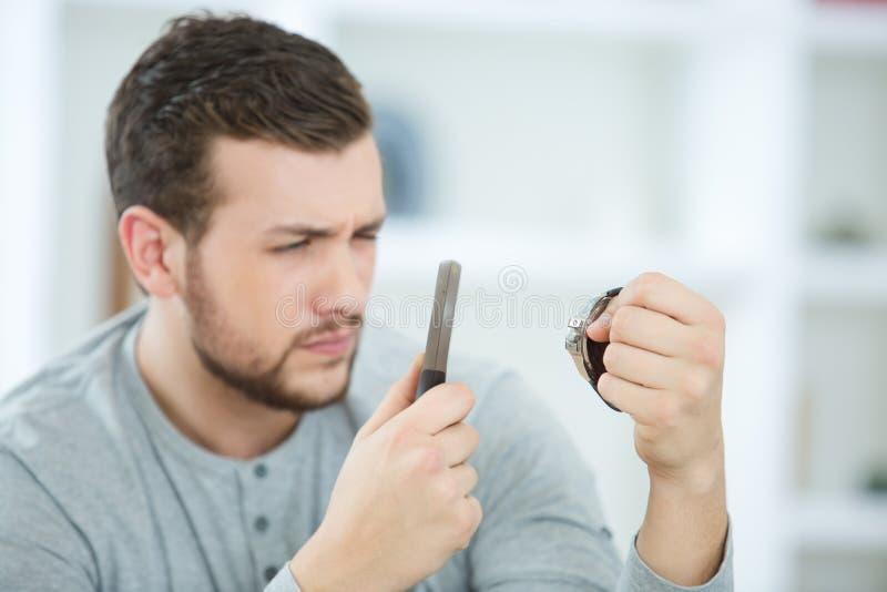 Młody człowiek patrzeje zegarek przez powiększać - szkło zdjęcie royalty free