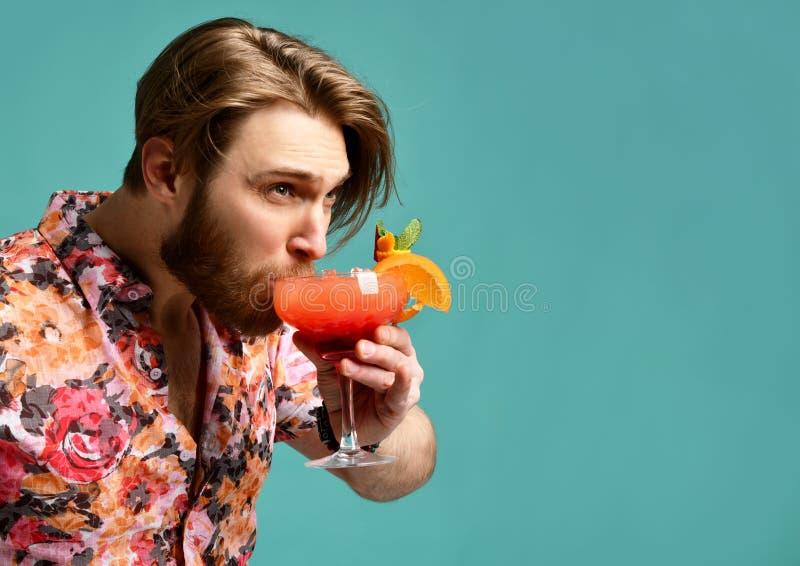 Młody człowiek pije czerwonego margarita koktajl w kapeluszu i okulary przeciwsłoneczni pijemy sok z pomarańczowy szczęśliwym pat fotografia stock