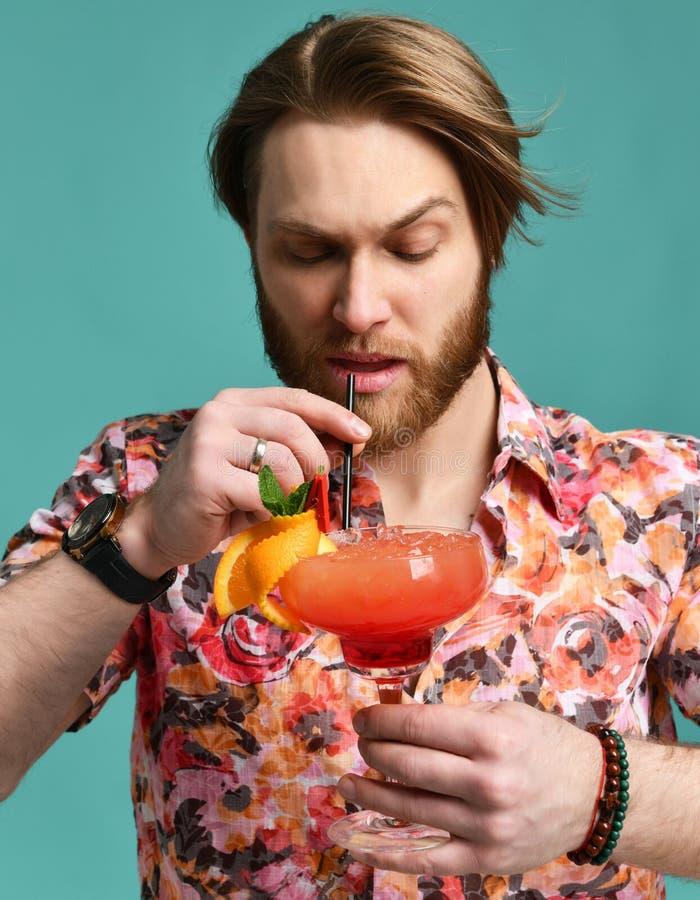 Młody człowiek pije czerwonego margarita koktajlu napoju sok z czarną słomą nad błękit mennicą obrazy royalty free