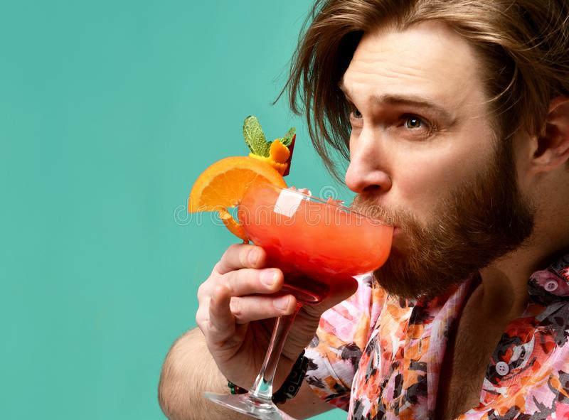 Młody człowiek pije czerwonego pomarańczowego margarita koktajlu napoju soku szczęśliwą patrzeje kamerę nad błękit mennicą zdjęcia stock