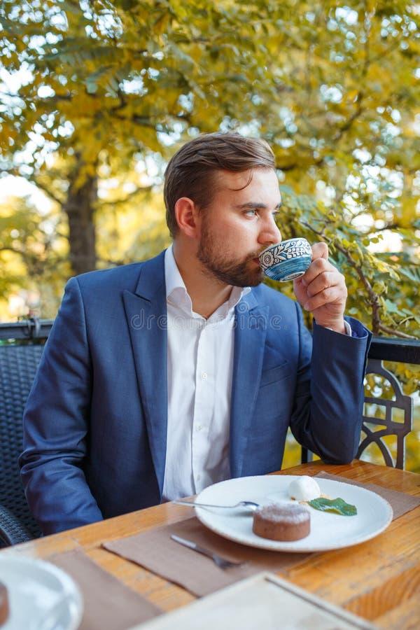 Młody człowiek pije herbaty z cukierkami na zamazanym naturalnym tle obraz royalty free