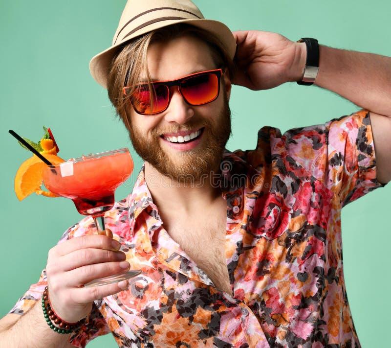 Młody człowiek pije margarita koktajl śmia się nad jasnozielonym w kapeluszu i okulary przeciwsłoneczni pijemy sok szczęśliwą pat obrazy stock