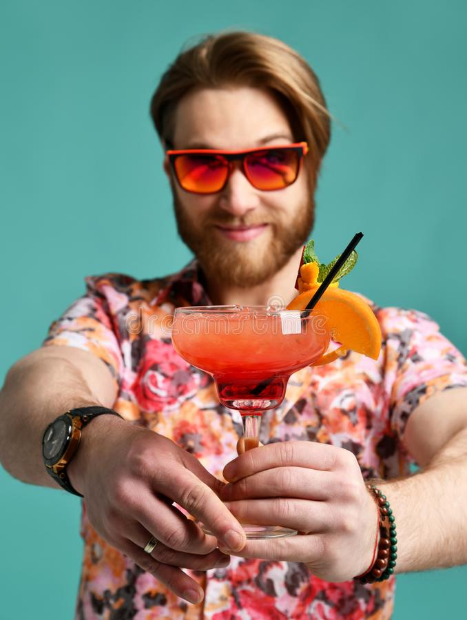 Młody człowiek pije margarita koktajl śmia się nad jasnozielonym w kapeluszu i okulary przeciwsłoneczni pijemy sok szczęśliwą pat zdjęcia royalty free
