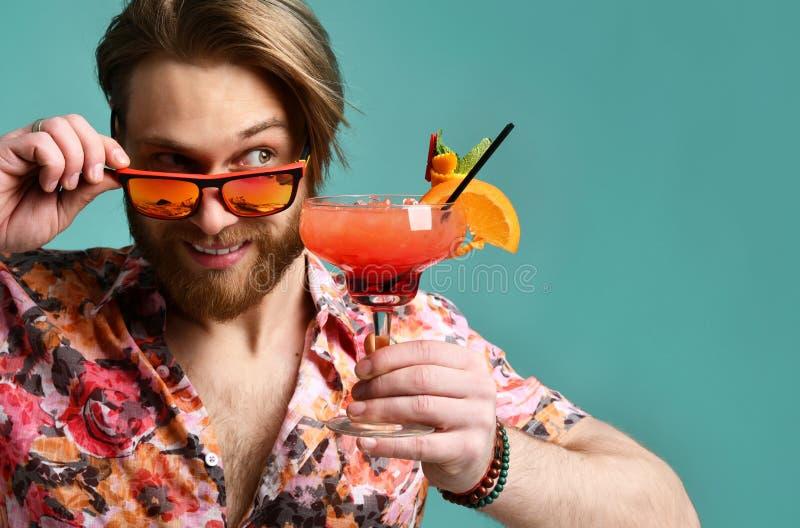 Młody człowiek pije margarita koktajl w czerwonych okularach przeciwsłonecznych pije sok szczęśliwego patrzejący kąta śmiać się zdjęcia stock