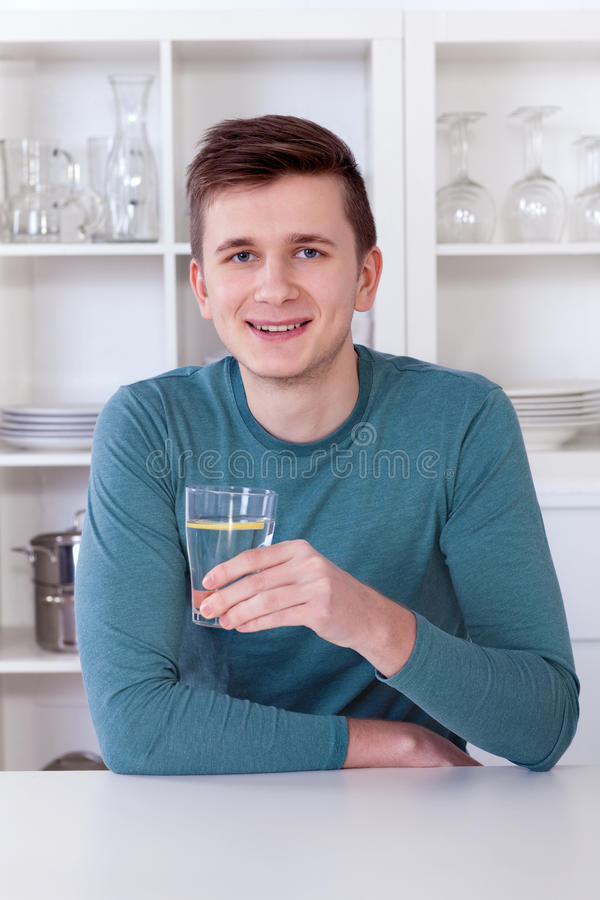 Młody człowiek pije odświeżającą lemoniadę w jego kuchni obraz stock