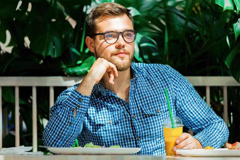 Młody człowiek pije sok w kawiarni obrazy stock
