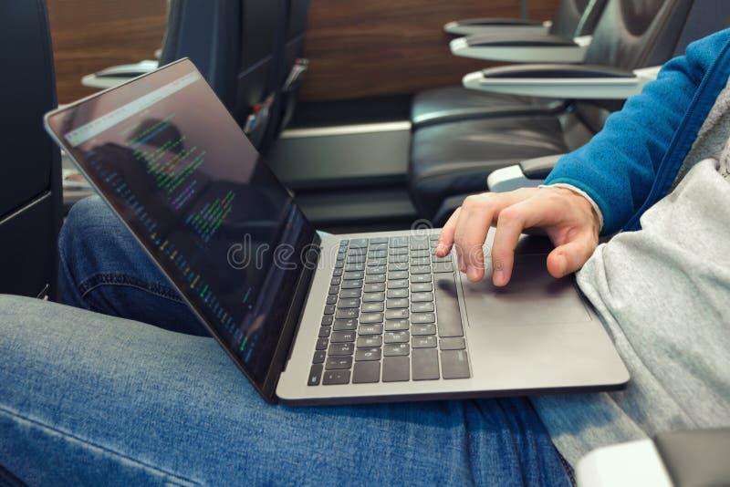 Młody człowiek pisze oprogramowanie kodzie na laptopie w transporcie w cajgach fotografia stock