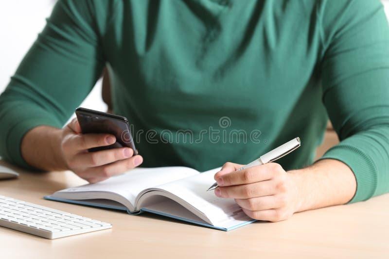Młody człowiek pisze w notatniku przy stołem z smartphone fotografia royalty free