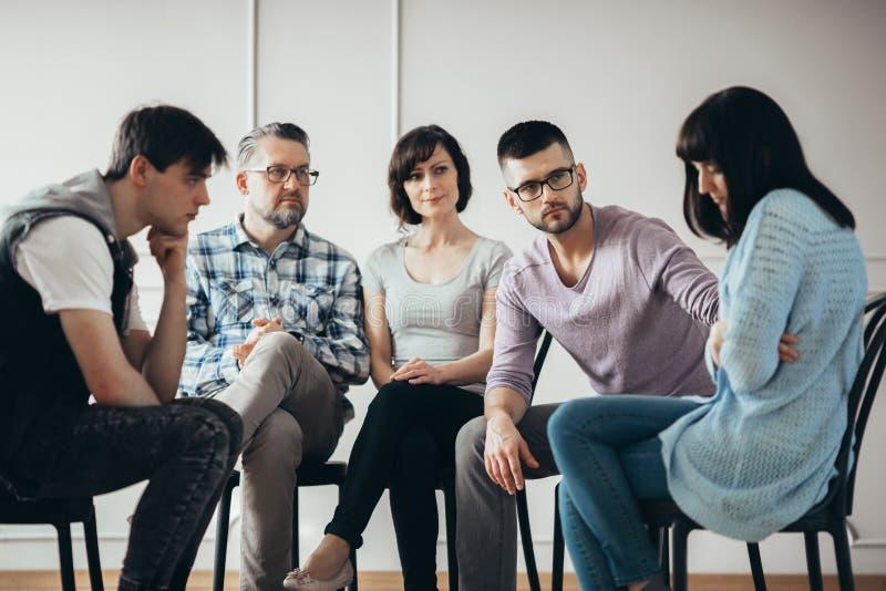 Młody człowiek pociesza opłakujący przyjaciela podczas grupowej terapii sesji zdjęcie stock