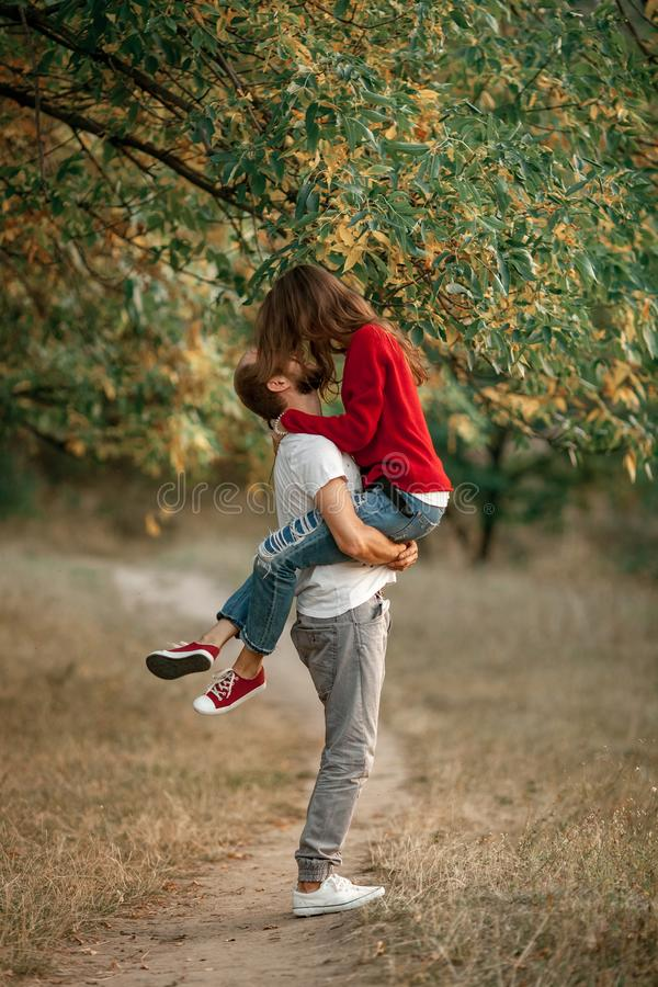 Młody człowiek podnoszący w górę dziewczyny w jego ręki i one całuje na spacerze w f obraz royalty free