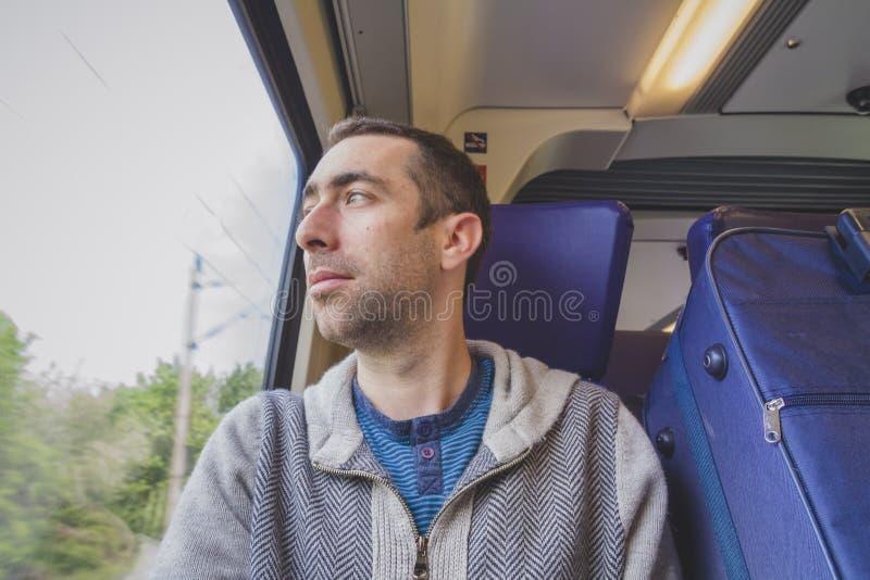 Młody człowiek podróżuje na pociągu i spojrzeniach out okno zdjęcie royalty free