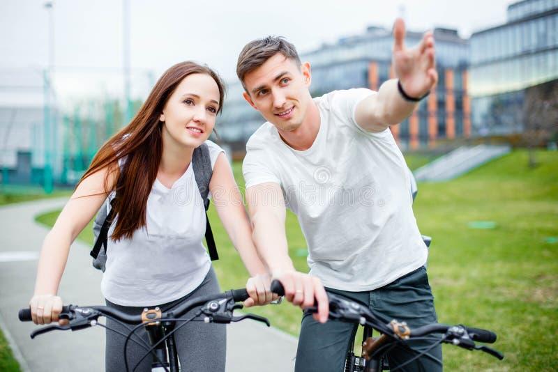 Młody człowiek pokazuje jego dziewczyny trasę Rowerowa wycieczka zdjęcia royalty free