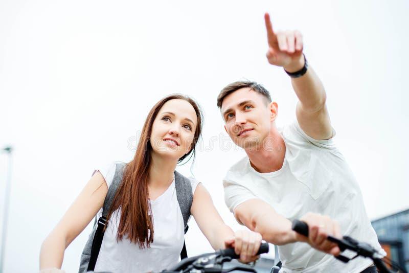 Młody człowiek pokazuje jego dziewczyny trasę Rowerowa wycieczka obraz stock