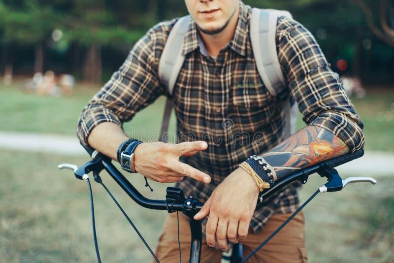 Młody Człowiek Pokazuje znaka pokoju Lub zwycięstwa obsiadanie Na bicyklu Na Zielonej lato łące fotografia royalty free