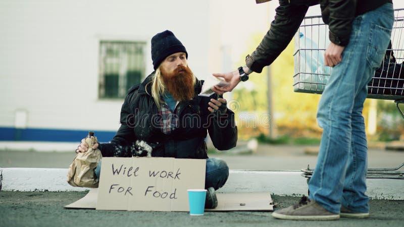 Młody człowiek pomaga, siedzi blisko wózek na zakupy przy podczas gdy żebraka napoju alkohol i bezdomna osoba i dawać on niektóre fotografia stock